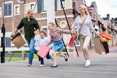 Famille tenant des mains et le fonctionnement avec des paniers sur le pont image stock