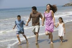 Famille tenant des mains tout en courant sur la plage Images stock