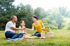 Famille très unie heureuse appréciant le pique-nique en parc Photographie stock libre de droits