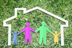 Famille traditionnelle heureuse dans leur maison sur le contexte de l'herbe verte Images stock