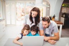 Famille travaillant sur l'ordinateur portable photographie stock libre de droits
