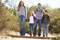 Famille trimardant dans des sacs à dos de port de campagne photographie stock libre de droits