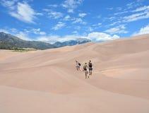 Famille trimardant dans les montagnes en voyage de vacances Photos libres de droits