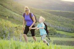 Famille trimardant dans les montagnes ensemble un bel été Photo stock