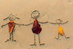 Famille, trois personnes dessinées sur le sable de plage Résumé Image libre de droits