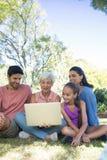 Famille utilisant l'ordinateur portable en parc Photo libre de droits