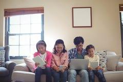 Famille utilisant l'ordinateur portable, le comprimé numérique et le téléphone portable dans le salon Photos stock