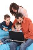 Famille utilisant l'ordinateur portatif Photos stock
