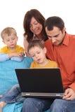 Famille utilisant l'ordinateur portatif Image libre de droits