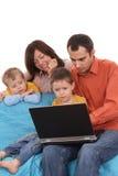 Famille utilisant l'ordinateur portatif Photographie stock