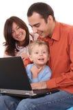 Famille utilisant l'ordinateur portatif Photo stock