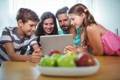 Famille utilisant le comprimé numérique tout en se reposant à la table Photographie stock