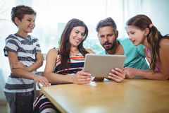 Famille utilisant le comprimé numérique tout en se reposant à la table Photos stock