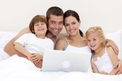 Famille utilisant un ordinateur portatif dans le bâti Photo libre de droits
