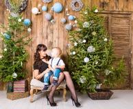 Famille, vacances et concept de Noël - mère et fils près de l'arbre de Noël Photographie stock libre de droits