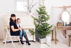 Famille, vacances et concept de Noël - mère et fils près de l'arbre de Noël Photo stock