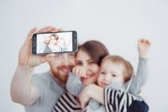 Famille, vacances, technologie et les gens - mère de sourire, père et petite fille faisant le selfie avec l'appareil-photo au-des Photo stock