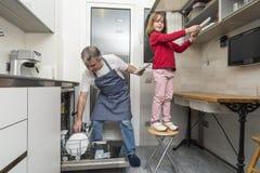 Famille vidant le lave-vaisselle Photographie stock