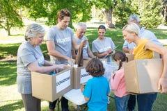 Famille volontaire heureuse séparant des substances de donations photo libre de droits