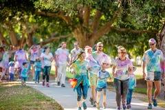 Familles appréciant la course d'amusement de frénésie de couleur images libres de droits
