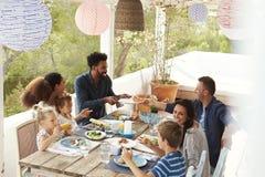 Familles appréciant le repas extérieur sur la terrasse ensemble Images libres de droits