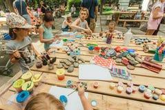 Familles avec des enfants jouant ainsi que des peintures et des crayons sur la table du terrain de jeu public Photographie stock libre de droits