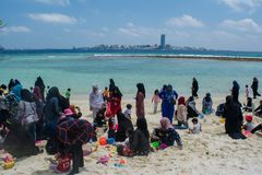 Familles musulmanes détendant à la plage tropicale en Maldives image libre de droits