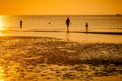 Familly on beach in orange sunset. Three part familly in distance on the sand beach in warm sunset Royalty Free Stock Image