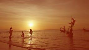 Familly entspannen sich während Sonnenuntergang durch den Strand Stockfoto
