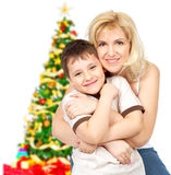 Family. Mother and son near Christmas tree. Isolated over white background Stock Photo