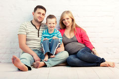 Family. Happy family of three sitting on the floor near the wall:  mother, father and little boy. Mother is pregnant Royalty Free Stock Photography