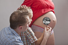 Family. Dad and son watching mums pregnant belly with magnifying glass royalty free stock photos