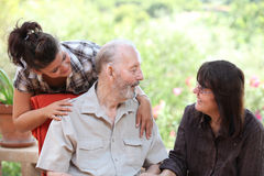 family. Granddaughter and daughter visiting happy smiling senior grandfather Stock Photography