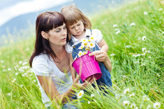 Family. Smiling mother and little daughter on nature. Happy people outdoors Stock Photo