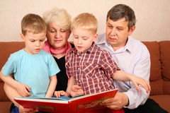 Family. Grandparents with grandchildren read book Stock Photography