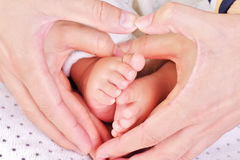 Family. Hands of parents holding the baby's feet, make a heart shape - concept for love Royalty Free Stock Image