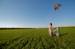 Family. The young girl with mother quickly runs on a green glade , fly a kite and happy smiles royalty free stock photo
