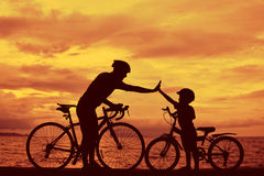 Family. Biker family silhouette at the beach at sunset royalty free stock photos
