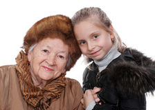 Family. Closeup portrait of senior women with little granddaughter in winter outwear on white background royalty free stock image