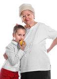 Family. Grandmother and young girl eating an apple smiling and embracing one another on white background stock photos