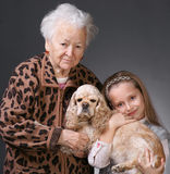 Family. Old women with her granddaughter and a dog (american spaniel) on a gray background royalty free stock images