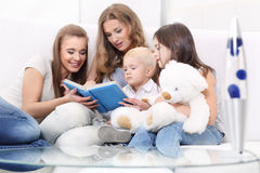 Reading children. Group of four people reading a book sitting in the living room Stock Photography