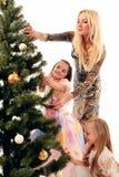 Family. Woman and girls embellish christmas tree royalty free stock photos