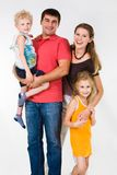 Family. Portrait of father holding boy with mother embracing daughter near by royalty free stock photography