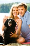 Family. Portrait of happy husband hugging his beautiful wife with black dog near by Royalty Free Stock Images