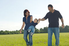 Family. Mother and Father Swinging Little Boy Royalty Free Stock Photos