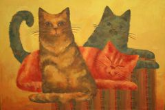 Family. Three home cats: black, red and brown sitting on a striped surface Royalty Free Stock Photos