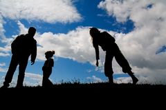 Family. Silhouettes of a small family on a hill with back light Stock Image