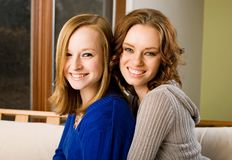 Family. Sisters ages fifteen and twenty one sit near each other on a sofa Stock Photo