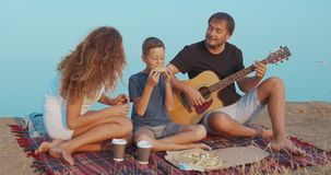 Family actively communicating while picnic on a hill and having snack with coffee and pizza. Family actively communicating while picnic on a hill and having stock footage